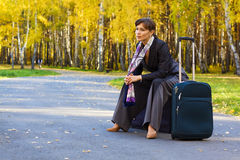 Business woman sitting on the suitcase Royalty Free Stock Image
