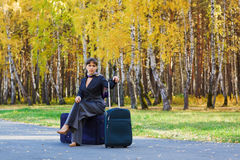 Businesswoman sitting on a luggage. Royalty Free Stock Photo