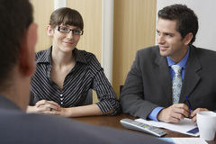 Businesswoman Sitting With Male Colleagues At Desk Royalty Free Stock Photos