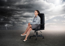 Businesswoman sitting in middle of opposite weather settings Royalty Free Stock Image