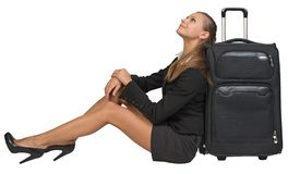Businesswoman sitting next to front view suitcase Stock Image