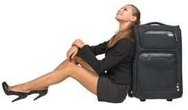 Businesswoman sitting next to front view suitcase Royalty Free Stock Photo