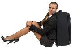 Businesswoman sitting next to side view suitcase Royalty Free Stock Images