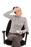 Businesswoman sitting in the office chair with headache holding Stock Photo