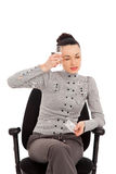 Businesswoman sitting in the office chair with headache holding Royalty Free Stock Photos