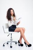 Businesswoman sitting on the office chair and holding notebook with pencil Stock Photos