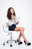 Businesswoman sitting on the office chair and holding notebook with pencil Royalty Free Stock Photo