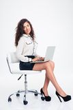 Businesswoman sitting on the office chair with laptop Royalty Free Stock Photo