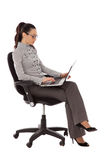 Businesswoman sitting in the office chair with laptop Royalty Free Stock Image