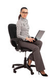 Businesswoman sitting in the office chair with laptop Royalty Free Stock Photography