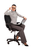 Businesswoman sitting in the office chair with laptop Stock Images