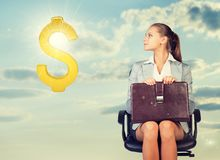 Businesswoman sitting on office chair, looking at Stock Images