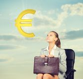 Businesswoman sitting on office chair, looking at Stock Photos