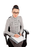 Businesswoman sitting in the office chair and siging documents Stock Photos