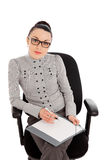 Businesswoman sitting in the office chair and siging documents Royalty Free Stock Photo