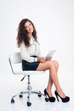 Businesswoman sitting on the office chair with tablet computer Royalty Free Stock Images