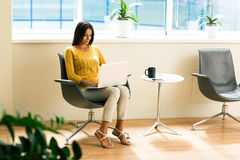 Businesswoman sitting on office chair and using laptop Stock Photo