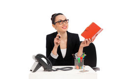 Businesswoman sitting in office chair and writing in notebook Royalty Free Stock Photography