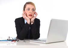 Businesswoman sitting at office desk working with laptop in stress looking upset. Attractive white blond businesswoman sitting at office desk working with laptop Stock Photos