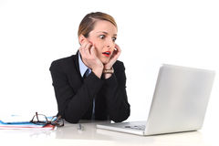 Businesswoman sitting at office desk working with laptop in stress looking upset. Attractive white blond businesswoman sitting at office desk working with laptop Stock Photo