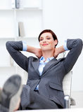 Businesswoman sitting in office with feet on desk Royalty Free Stock Image