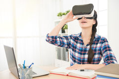 Businesswoman sitting in office and holding VR Royalty Free Stock Photos