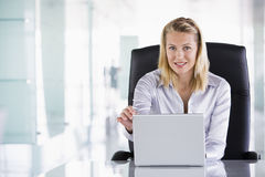 Businesswoman sitting in office with laptop Stock Images