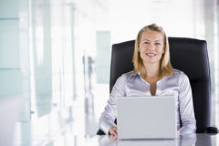 Businesswoman sitting in office with laptop Stock Photo