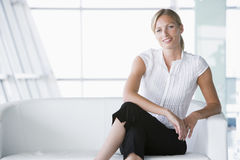 Businesswoman sitting in office lobby smiling Stock Photos