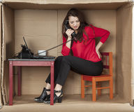 Businesswoman sitting in the office and talking on the phone Stock Images
