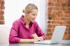 Businesswoman sitting in office using laptop Stock Photography