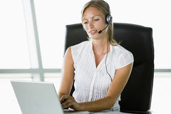 Businesswoman sitting in office wearing headset Stock Photography