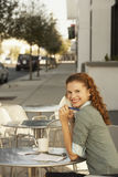 Businesswoman Sitting At Outdoor Cafe Table. Portrait of happy young businesswoman sitting at outdoor cafe table Stock Image