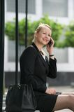 Businesswoman sitting outdoors and calling by phone Stock Image