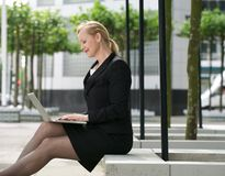Businesswoman sitting outside with laptop Royalty Free Stock Photos