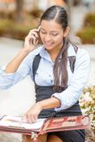 Businesswoman sitting outside reviewing financial statements paperwork talking on mobile phone Royalty Free Stock Photography