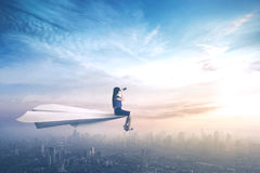 Businesswoman sitting on paper aeroplane Stock Images