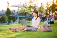 Businesswoman sitting in park working on laptop, sunny summer da Royalty Free Stock Photos