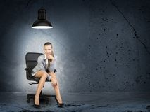 Businesswoman sitting in poorly lighted room Stock Image