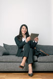 Businesswoman sitting reading a tablet-pc Royalty Free Stock Images