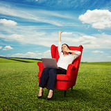 Businesswoman sitting in red chair with laptop Royalty Free Stock Image