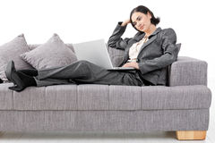 Businesswoman sitting on sofa. Young businesswoman sitting on sofa, working with laptop computer. Isolated on white background Stock Images