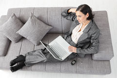 Businesswoman sitting on sofa. Young businesswoman sitting on sofa, working with laptop computer. Isolated on white background Stock Photography