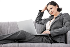 Businesswoman sitting on sofa. Young businesswoman sitting on sofa, working with laptop computer. Isolated on white background Royalty Free Stock Image