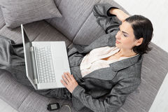 Businesswoman sitting on sofa. Young businesswoman sitting on sofa, working with laptop computer. Isolated on white background, overhead view Stock Photos