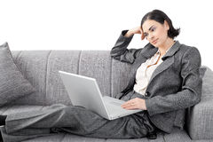 Businesswoman sitting on sofa. Young businesswoman sitting on sofa, working with laptop computer. Isolated on white background Royalty Free Stock Photos