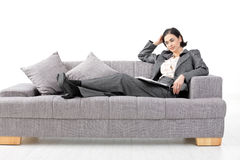 Businesswoman sitting in sofa. Young businesswoman sitting on sofa, working Royalty Free Stock Image