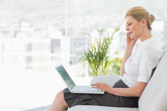 Businesswoman sitting on the sofa with laptop Royalty Free Stock Photo