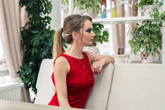 Businesswoman sitting on the sofa at the restaurant. Lady in red. Businesswoman sitting on the sofa at the restaurant. Blonde lady in red. She is waiting for a Stock Images