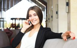 Businesswoman sitting sofa using smartphone in coffee shop. Royalty Free Stock Photo